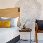 Bed, side table, and chair in BEI San Francisco room