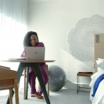 Woman sitting at a table look at laptop next to a window in hotel room