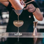 Cocktail in stemmed glass being strained by bartender