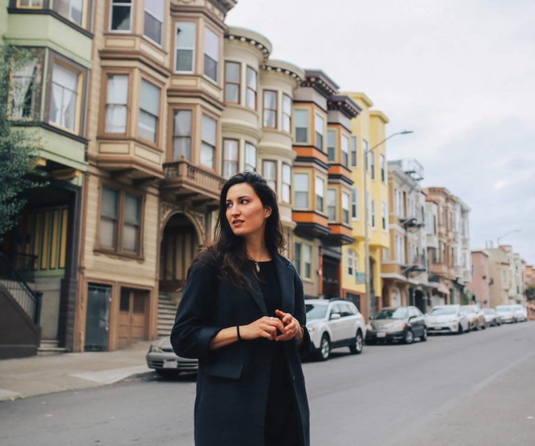 woman takes in the sites while walking among San Francisco's Painted Lady houses