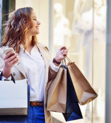 woman window shops while carrying her some of her earlier purchases