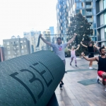 close crop of a yoga mat with the BEI logo, and people doing yoga in the background