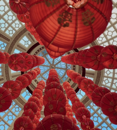 a series of red chinese paper lanterns hang in a glass dome, shot looking up
