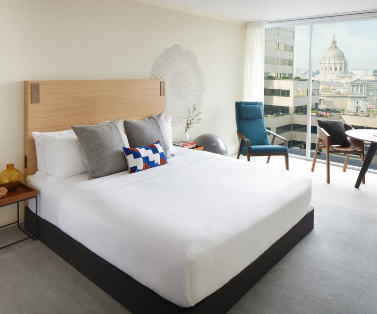 hotel room with large white bed and seating area by window