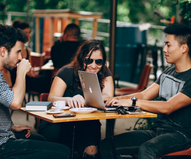 three people sit on a patio drinking coffee and using a computer