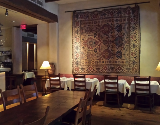 Kokkari restaurant interior with tables and wall tapestry