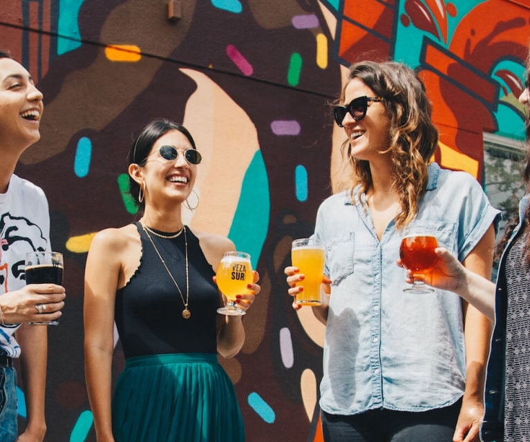 group of women drink and laugh next to gratified wall.