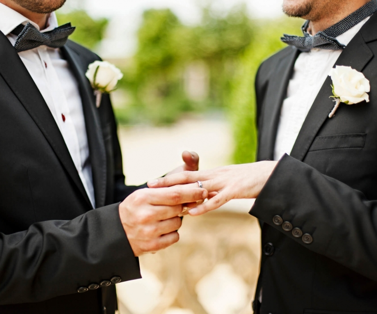 two men exchange wedding bands in suits and bow ties