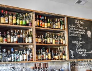 bar with three shelves full of liquor bottles