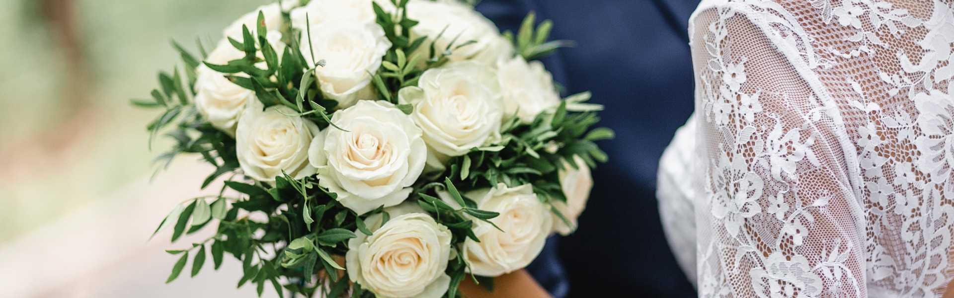 close up of wedding bouquet with bride and groom embracing