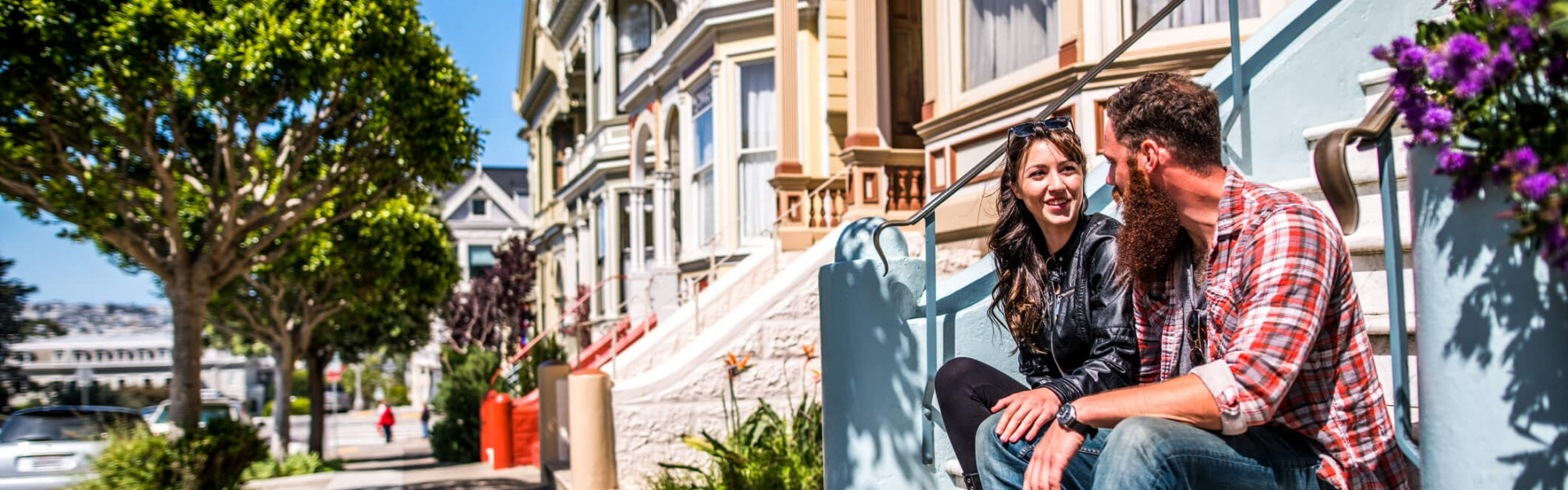 couple sits on stoop of painted lady home with corgi