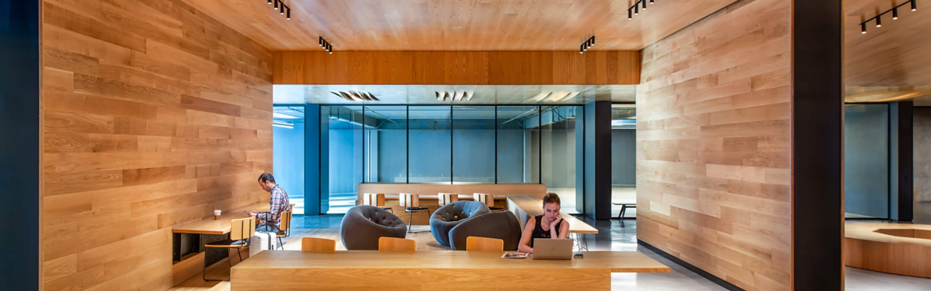 people gather in communal workspace which is entirely wooden and modern
