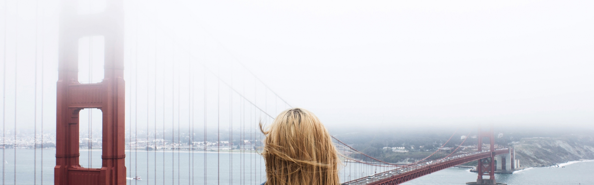 woman stand and looks at golden gate bridge in the fog