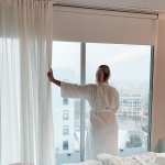 woman stares out of window in white bathrobe